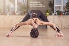 Junges athletisches Mädchen, das Yogaübungen ausdehnend tut Mit den barfüßigbeinen stehen auseinander und Hände gehen das Berühre lizenzfreies stockbild