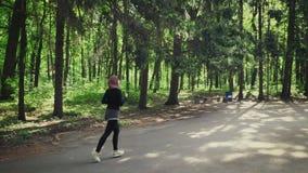 Junges athletisches Mädchen in hijab Betrieb, rüttelnd im grünen Park, Seitenansicht 50 fps stock video