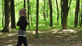 Junges athletisches Mädchen in hijab Betrieb, rüttelnd im grünen Park, Seitenansicht 50 fps stock footage