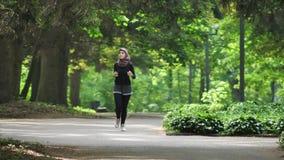 Junges athletisches Mädchen in hijab Betrieb, rüttelnd im grünen Park, Vorderseiteansicht 50 fps stock video