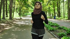 Junges athletisches Mädchen in hijab Betrieb, rüttelnd im grünen Park, Vorderseiteansicht 50 fps stock footage