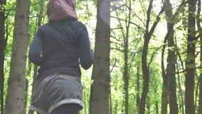 Junges athletisches Mädchen in hijab Betrieb, rüttelnd im grünen Park, Wald, hintere Unterseitenansicht 50 fps stock video