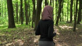 Junges athletisches Mädchen in hijab Betrieb, rüttelnd im grünen Park, Wald, Rückseiteansicht 50 fps stock video footage
