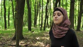 Junges athletisches Mädchen in hijab Betrieb, rüttelnd im grünen Park, Wald, Vorderseiteansicht 50 fps stock video footage
