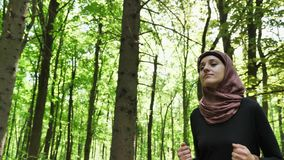 Junges athletisches Mädchen in hijab Betrieb, rüttelnd im grünen Park, Wald, Vorderseiteansicht 50 fps stock footage