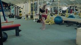 Junges athletisches M?dchen steht auf ihren H?nden, die eine akrobatische Bremsung durchf?hren stock footage