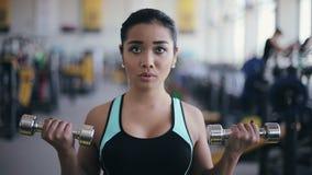 Junges attraktives asiatisches Mädchen, das Übung mit Dummköpfen tut stock video