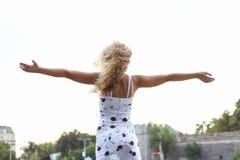 Junges attraktives blondes Mädchen, das ihre Arme verbreitet Lizenzfreie Stockfotos