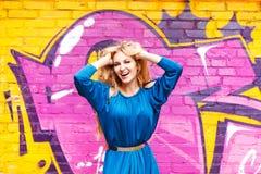 Junges attraktives blondes Mädchen nahe der Wand mit Graffiti Lizenzfreie Stockbilder