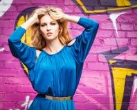 Junges attraktives blondes Mädchen nahe der Wand mit Graffiti Stockfotos