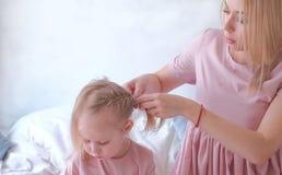 Junges attraktives blondes Mutterbindungshaar in Zöpfe zu ihrer kleinen reizend Tochter im Rosa kleidet während sie Malerei mit a Lizenzfreies Stockfoto