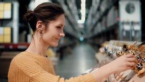 Junges attraktives Brunettemädchen wählt im Geschäft Dekor des strahlenden Golds Weihnachts Lizenzfreies Stockbild