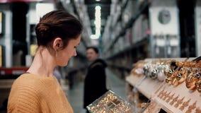 Junges attraktives Brunettemädchen wählt im Geschäft Dekor des strahlenden Golds Weihnachts stock footage