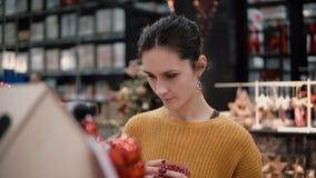 Junges attraktives Brunettemädchen wählt im Geschäft hellen roten Weihnachtsdekor Stockfoto