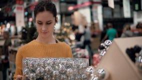 Junges attraktives Brunettemädchen wählt im Geschäft hellen Spielwaren Weihnachtsdekor Lizenzfreie Stockbilder