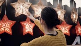 Junges attraktives Brunettemädchen wählt im Geschäft Lampen Stern-Lichter, Weihnachtsdekor Stockbild