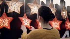 Junges attraktives Brunettemädchen wählt im Geschäft Lampen Stern-Lichter, Weihnachtsdekor Stockfotografie