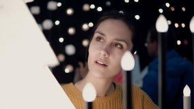 Junges attraktives Brunettemädchen wählt im Geschäft Lampen, Weihnachtsdekor Stockfotos