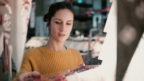Junges attraktives Brunettemädchen wählt im Geschäft Lampen, Weihnachtsdekor Stockbild