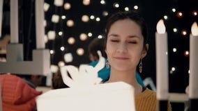 Junges attraktives Brunettemädchen wählt im Geschäft Lampenkastenlichter, Weihnachtsdekor Lizenzfreie Stockbilder