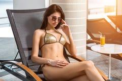Junges attraktives dünnes Mädchen im Bikini, der auf Klappstuhl im Wellnessbadekurort-Hotelerholungsort sich entspannt stockfotografie