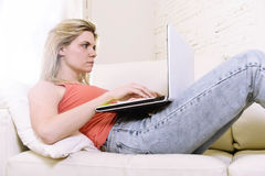 Junges attraktives Frauenlügen des blonden Haares bequem auf Hauptsofa unter Verwendung des Internets in der Laptop-Computer Lizenzfreies Stockfoto