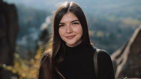 Junges attraktives Frauenporträt des Porträts, das die Kamera in den Bergen untersucht Schöner Felsen-Hintergrund draußen stock footage