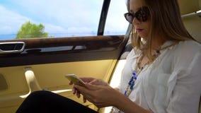 Junges attraktives Geschäftsfraureiten im Taxi und surfendes Netz auf Smartphone stockfoto