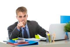 Junges attraktives Geschäftsmannarbeiten beschäftigt mit Laptop-Computer im Büro, das mit seinem Finger zeigt Lizenzfreie Stockfotografie