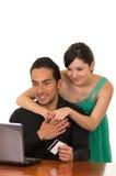 Junges attraktives glückliches Paar vor Computer Lizenzfreie Stockfotos