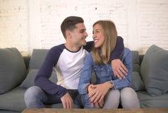 Junges attraktives glückliches und romantisches Couchlächeln des Paarfreund- und -freundinumarmungsangebots zu Hause spielerisch  stockfotografie