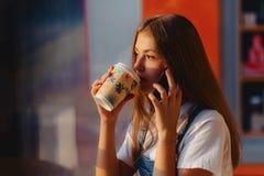Junges attraktives hübsches Mädchen am Café mit Kaffee und Telefon an MO stockfotos