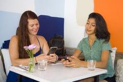 Junges attraktives hispanisches Mädchen, das am modernen Café mit roter Haarunternehmerfrau in den Freundinnen sich treffen für u lizenzfreie stockfotos