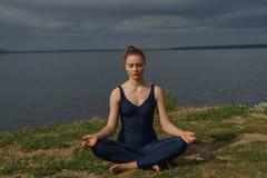Junges attraktives lächelndes übendes Yoga der Frau, sitzend in halber Lotus-Übung, Haltung Ardha Padmasana stockfotografie