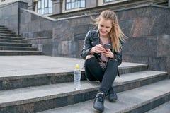 Junges attraktives lächelndes Mädchen in einer Lederjacke und in Jeans, die in der Hand auf der Treppe mit einem Smartphone sitze stockbild
