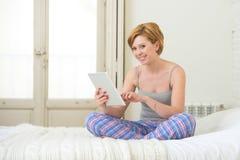 Junges attraktives Mädchen, beim Schlafen keucht das Sitzen auf Bett unter Verwendung der digitalen Tablettenauflage des Internet stockfotos