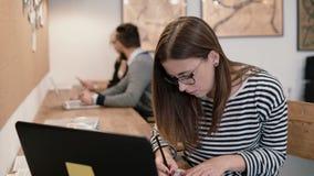 Junges attraktives Mädchen benutzt einen Laptop und arbeitet mit den Dokumenten und macht Anmerkungen im modernen Startbüro Lizenzfreie Stockbilder