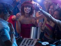 Junges attraktives Mädchen, das an der Partei mit DJ lacht Lizenzfreies Stockfoto