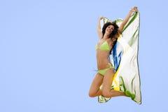 Junges attraktives Mädchen, das mit Brasilien-Flagge in der Luft springt Stockfoto
