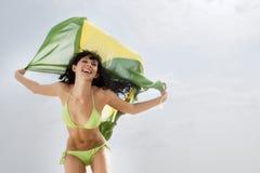 Junges attraktives Mädchen, das mit Brasilien-Flagge in der Luft springt stockbilder