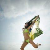 Junges attraktives Mädchen, das mit Brasilien-Flagge in der Luft springt stockbild