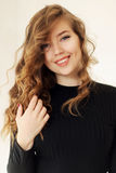 Junges attraktives Mädchen, das mit Grübchen und Locken blonden ha lächelt lizenzfreie stockbilder