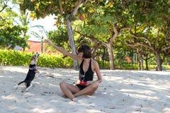 Junges attraktives Mädchen, das mit ihrem Schoßhund Spürhund am Strand von Tropeninsel Bali, Indonesien spielt Glückliche Momente stockbild