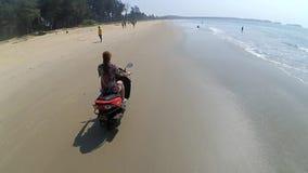 Junges attraktives Mädchen, das Roller auf dem Strand nahe dem Wasser während des Sonnenuntergangs fährt Hubschrauber jagt einen  stock footage