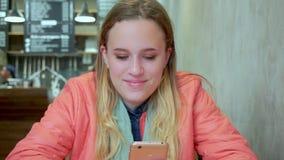 Junges attraktives Mädchen, das Smartphone im Café schaut Sie lächelt stock footage