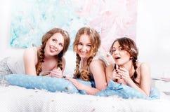 Junges attraktives Mädchen in den Pyjamas, die auf dem Bett und dem Lächeln liegen f Stockfoto