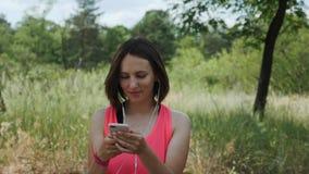 Junges attraktives Mädchen im rosa Hemd mit hörender Musik der Kopfhörer auf Smartphone Sportives brunette Mädchentanzen im Park  stock video footage