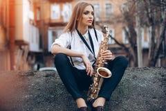 Junges attraktives Mädchen im weißen Hemd mit einem Saxophonsitzen sitzt auf der Erde - im Freien Sexy junge Frau mit Saxophon de Stockfoto