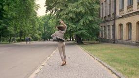 Junges attraktives Mädchen ist, springend tanzend und auf Bürgersteig in der Tageszeit, im Sommer, Bewegungskonzept stock footage