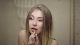 Junges attraktives Mädchen mit langem Haarfärbemittellippenstift vor einem Spiegel stock video